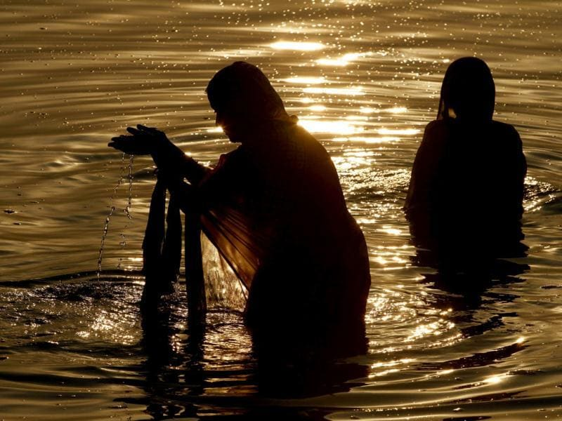 Indian Hindu women offer prayers after taking a holy dip in the river Yamuna, in Allahabad.