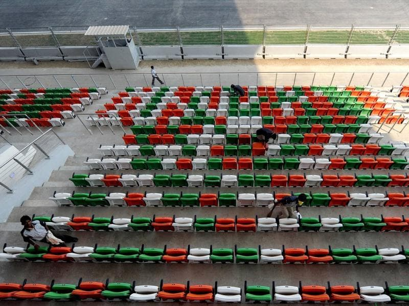 Workers clean spectator seats of the main grand stand at the newly-inaugurated Buddh International Circuit ahead of the Indian Grand Prix in Greater Noida.