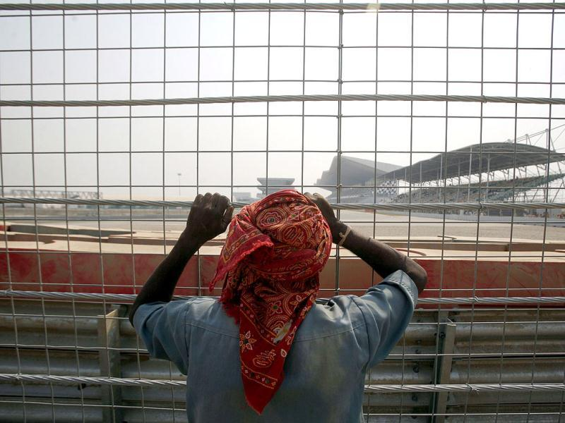 A labourer stands behind a fence as he looks out at the Buddh International Circuit, the venue for the first ever Indian Formula One race at Greater Noida.