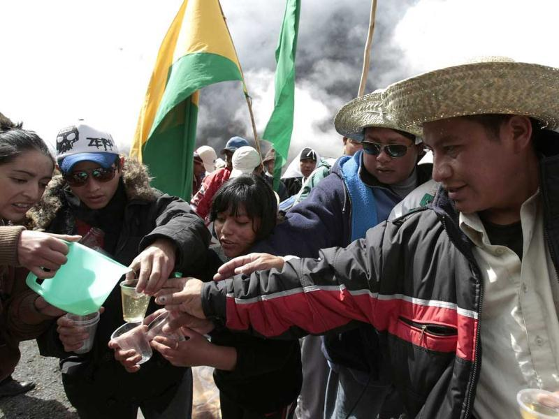 Bolivian indigenous people from the Isiboro Secure Territory, known by its Spanish acronym TIPNIS, receive a drink near La Cumbre, in the outskirts of La Paz.