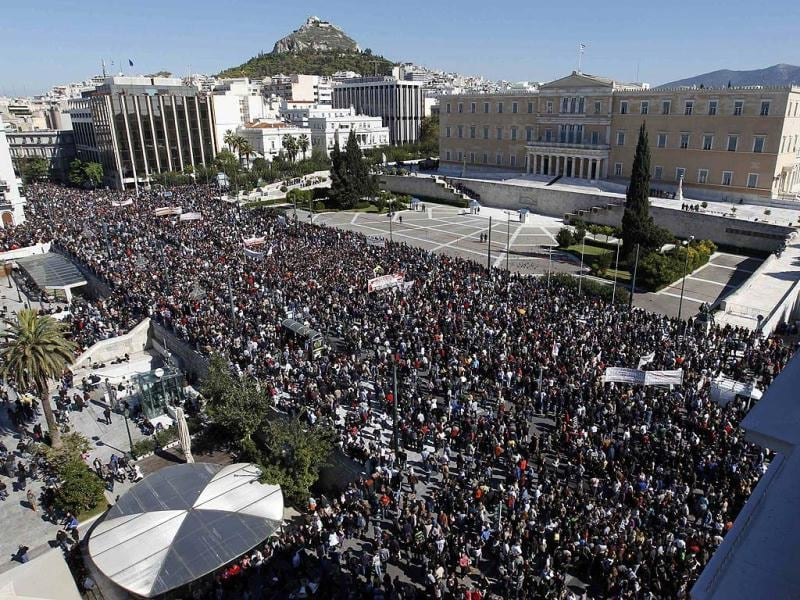 People walk past the Greek parliament during an anti-austerity rally in Athens' Syntagma (Constitution) square. Greek unions begin a 48-hour general strike on the biggest protest in years.