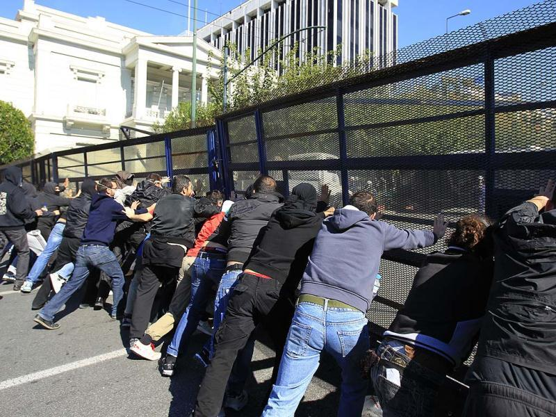 Demonstrators push a metallic police barrier outside the Greek Parliament. A two-day general strike that unions vow will be the largest in years grounded flights, disrupted public transport and shut down everything from shops to schools in Greece.