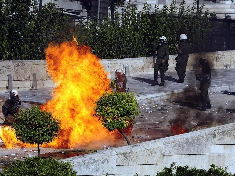 Protesters throw petrol bombs at riot police in front of the Greek Parliament in Athens at the start of a two-day general strike against a new austerity bill.