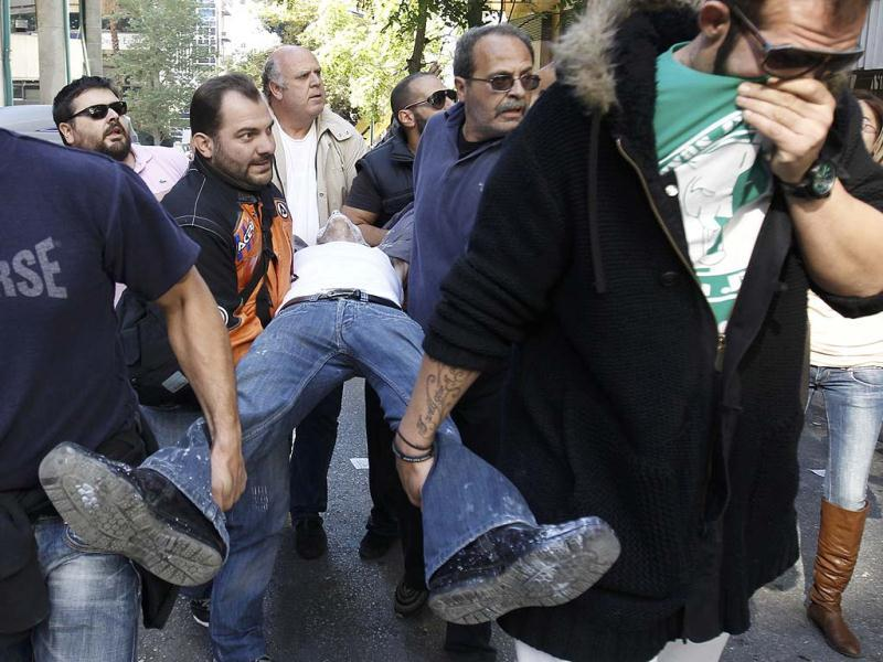 An injured anti-austerity demonstrator is carried to safety during clashes with riot police in Athens' Syntagma (Constitution) square.