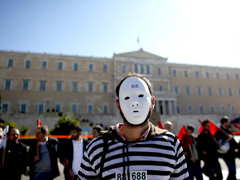 A demonstrator stands in front of the Greek parliament in Athens as a two-day general strike began against a new austerity bill.