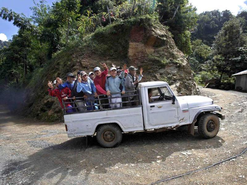 Ziona's family members wave from a vehicle on their way to a church construction site in Baktawng village in Mizoram. (Reuters)