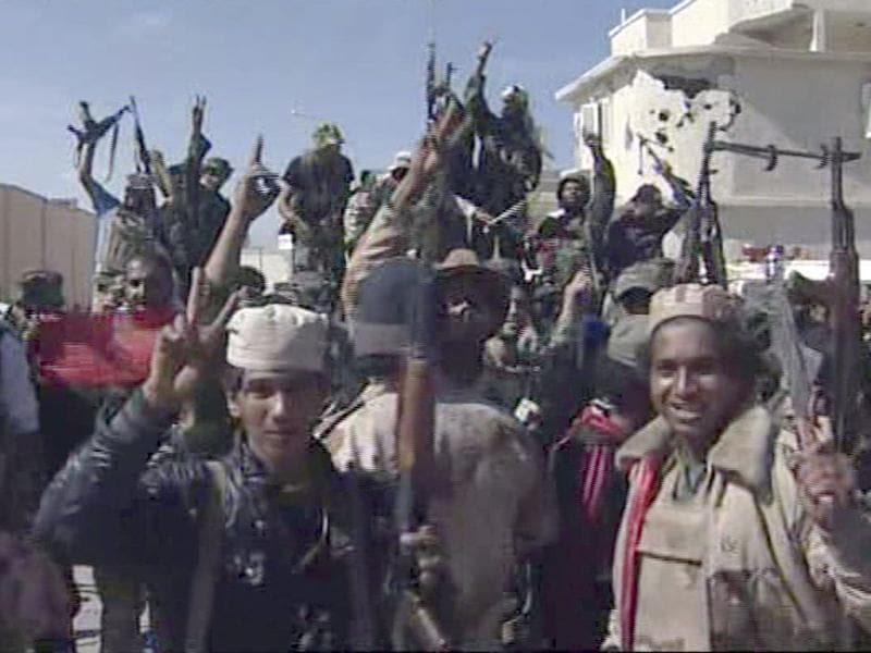 Libyan fighters celebrate in the streets of Sirte, Libya in this image taken from TV. (AP)