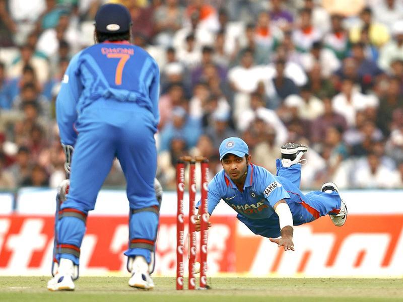Ajinkya Rahane (R) dives as he throws the ball in an unsuccessful attempt to run out England's Ravi Bopara (unseen) during India's third one-day international cricket match in Mohali.