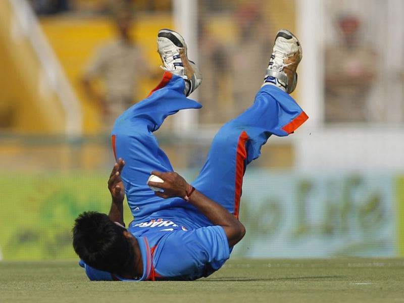 Vinay Kumar falls on the ground in an attempt to field the ball during India's third one-day international cricket match against England in Mohali.