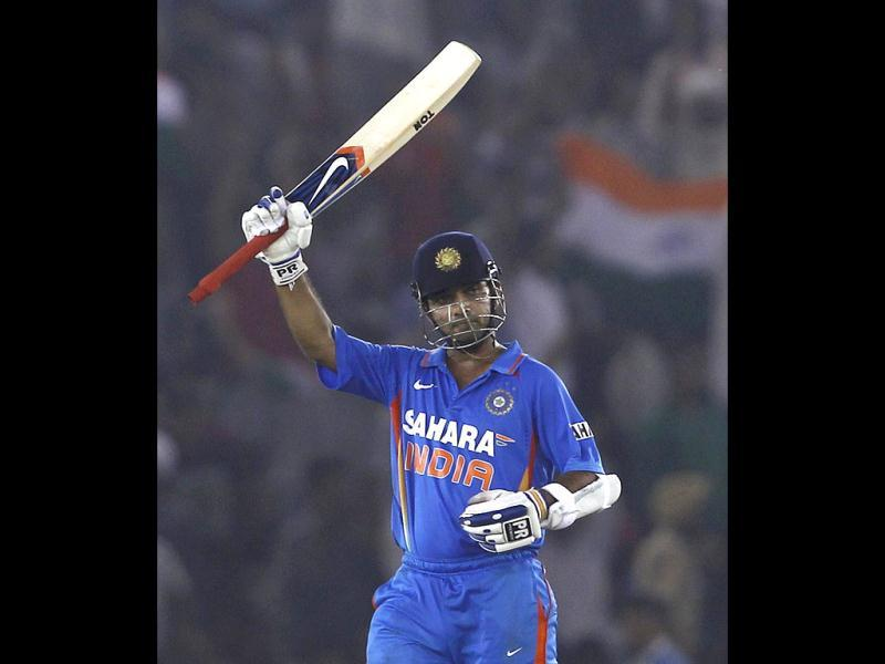 Ajinkya Rahane raises his bat to celebrate scoring his half century during their third one-day international cricket match against England in Mohali.