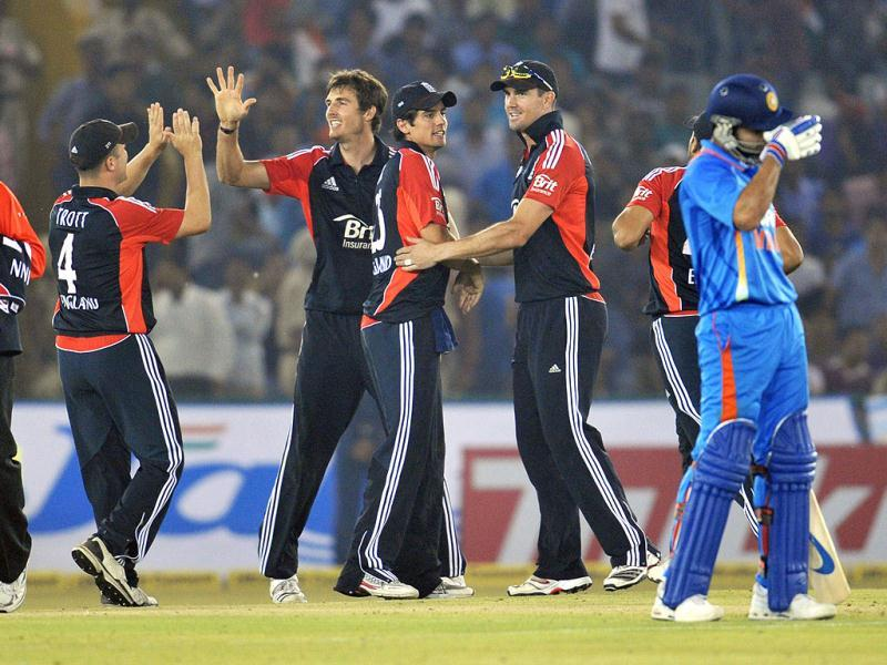 England bowler Steven Finn (C) celebrates with teammates after he dismissed Indian batsman Ajinkya Rahane during the third one day international cricket match between India and England at The Punjab Cricket Association (PCA) Stadium in Mohali.