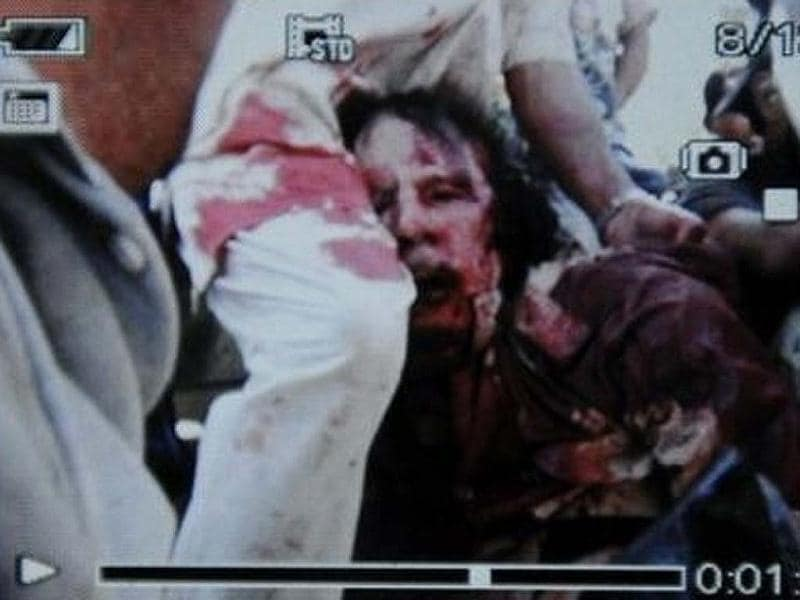 Former Libyan leader Muammar Gaddafi, covered in blood, is held on a truck by NTC fighters in Sirte in this still image taken from video footage.