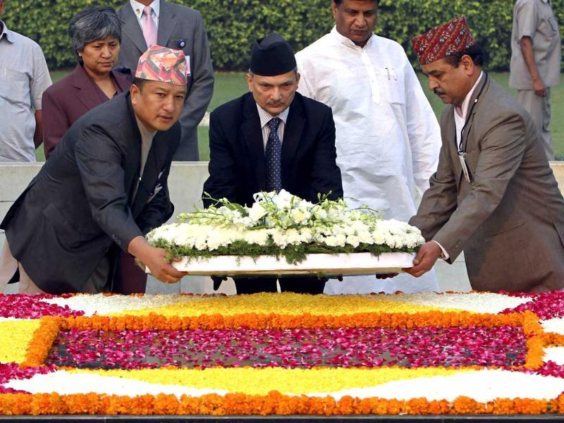 Nepal's Prime Minister Baburam Bhattarai (C) places a wreath at the Mahatma Gandhi memorial as his wife Hisila Yami (back L) watches at Rajghat in New Delhi. (Reuters)