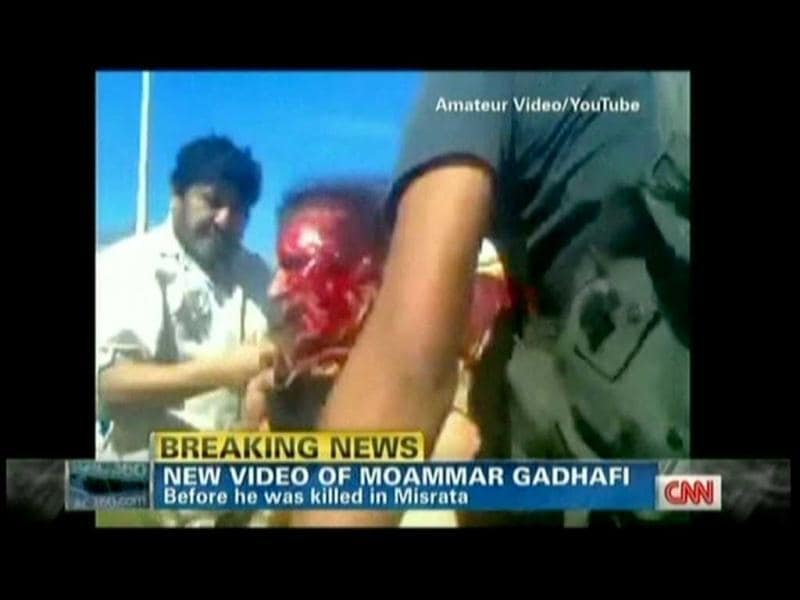 In this TV grab from YouTube courtesy CNN, Muammar Gaddafi is seen covered in blood moments after he was captured by Libyan rebel forces in his hometown Sirte. (AFP)