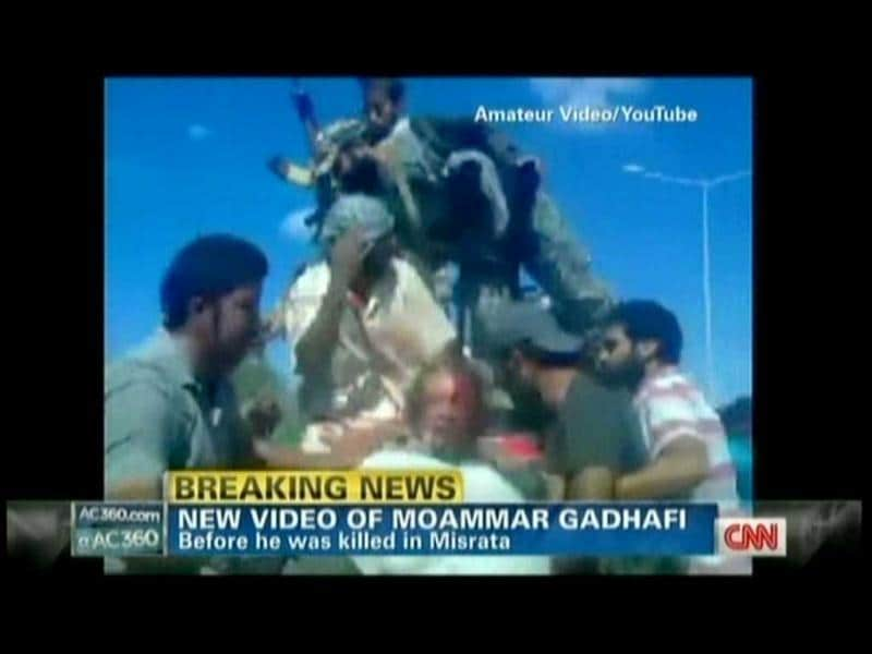 Muammar Gaddafi is seen atop a vehicle moments after he was captured by Libyan rebel forces. TV grab from YouTube courtesy CNN (AFP)