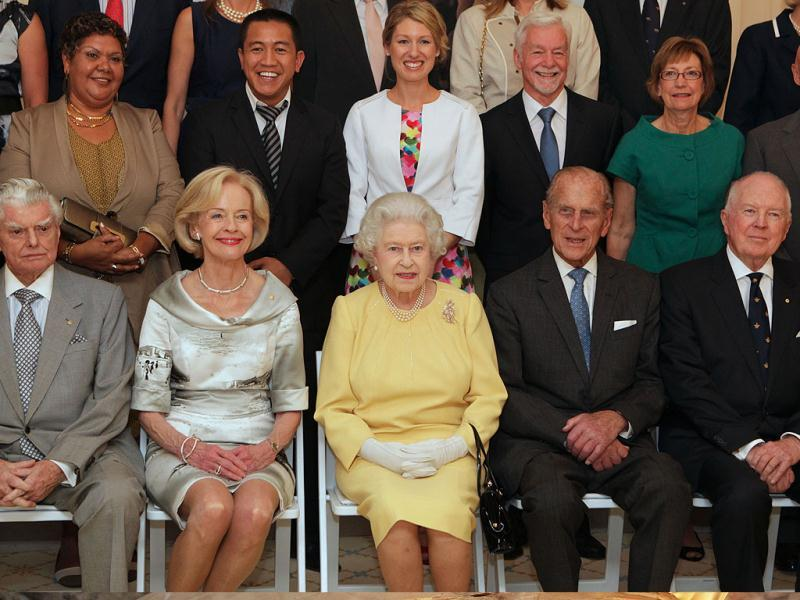 Britain's Queen Elizabeth II, sitting at center, and her husband the Duke of Edinburgh, second right, Governor-General Quentin Bryce, second left, with guests who were invited to a lunch hosted by Bryce at Government House in Canberra, Australia, pose for a group photo.
