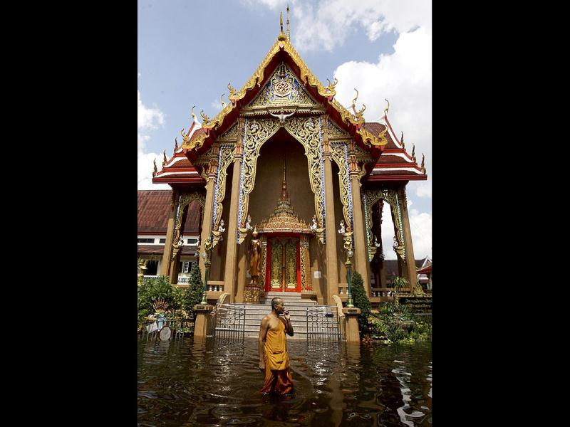A Thai Buddhist monk smokes a cigarette as he wades along the flooded Weeru Wanaram temple at Don Muang District, in Bangkok, Thailand. Thailand's catastrophic floods may take up to six weeks to recede, Prime Minister Yingluck Shinawatra said.