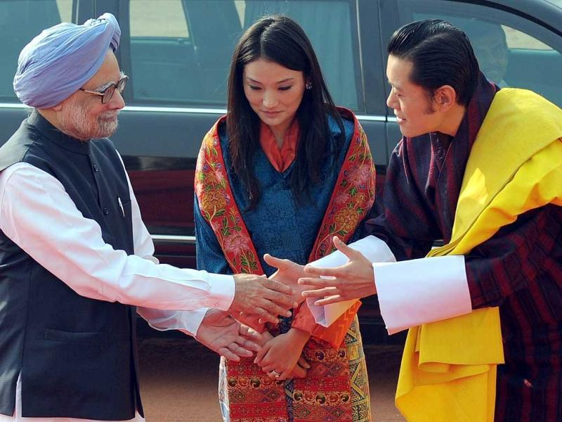 Bhutan's Queen Jetsun Pema (C) watches as King Jigme Khesar Namgyel Wangchuck (R) shakes hands with Prime Minister Manmohan Singh (L) during a ceremonial reception at the Presidential Palace in New Delhi. Bhutan's King Jigme Khesar Namgyel Wangchuck and his newlywed queen Jetsun Pema, are on a nine-day state visit to India.