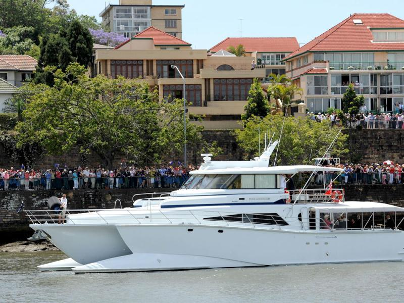 Queenslanders cheer as Britain's Queen Elizabeth II passes on the catamaran 'Pure Adrenalin' during the royal boat tour along the Brisbane River.