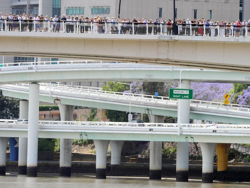Residents line the Riverside freeway to see Britain's Queen Elizabeth II as she passes on the catamaran 'Pure Adrenalin' during the royal boat tour along the Brisbane.
