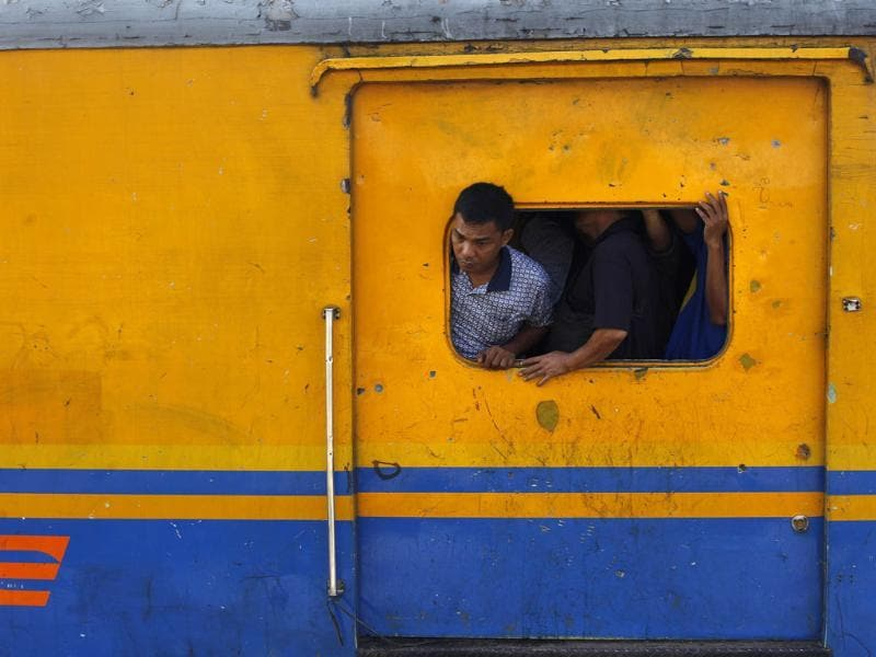A passenger looks out of a window on a cargo train at Tanah Abang train station in Jakarta.