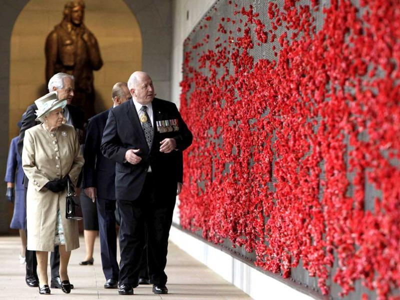 Britain's Queen Elizabeth II (L) is accompanied by General (Retired) Peter Cosgrove (R), chairman of the Australian War Memorial Board, as she walks the cloisters at the Australian War Memorial in Canberra.