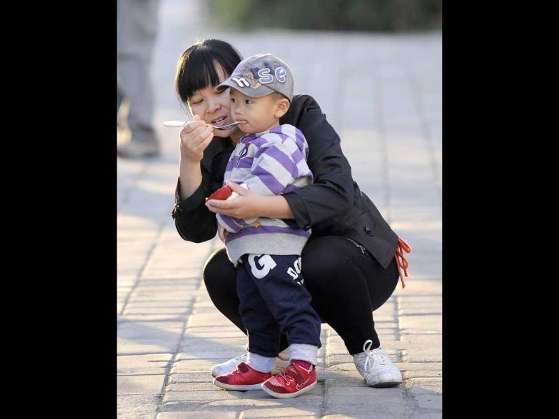 A mother feeds her baby in Beijing. China's one-child policy has prevented almost half a billion births but has turned into a demographic time bomb as the population ages, storing up huge economic and social problems for the country.