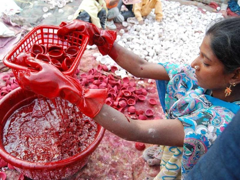 Randeep Kaur a labour dips earthen lamps into red paint in Amritsar ahead of the Diwali festival in Amritsar.