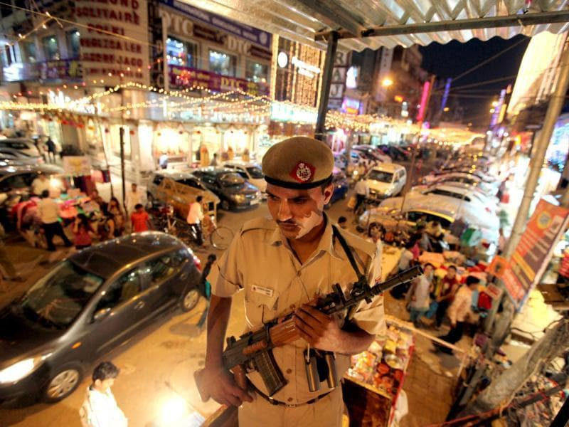 A Delhi Police officer stands guard at a city market on the eve of Diwali. (HT Photo/Rajkraj)