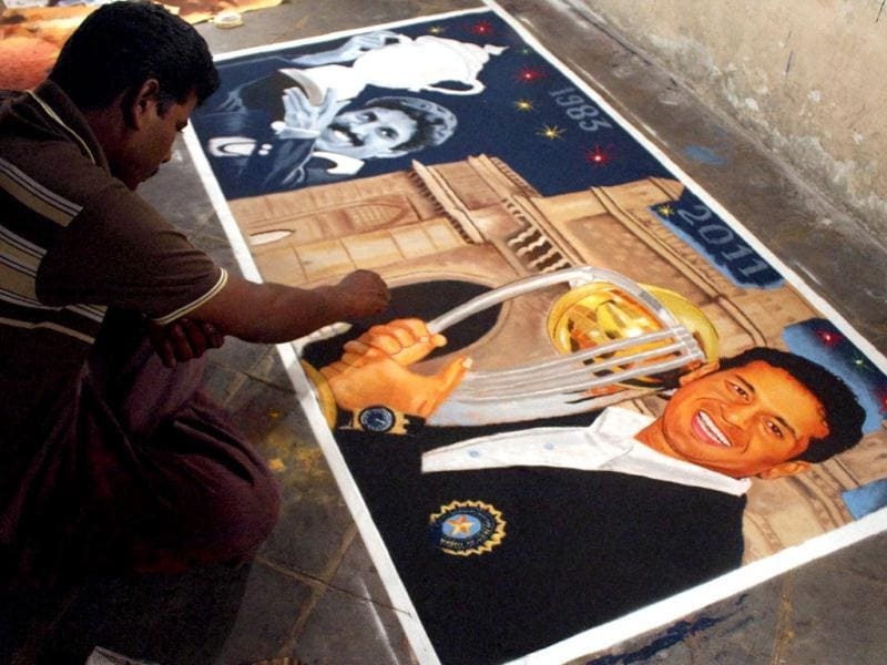 An artist gives finishing touches to a rangoli of Sachin Tendulkar and Kapil Dev, on the eve of Diwali at Thane in Mumbai. (PTI)