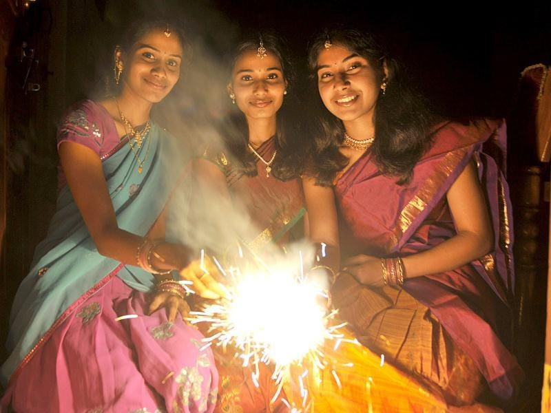 Hindu women pose with sparklers at the entrance to their home on the eve of Diwali in Hyderabad. (AFP)