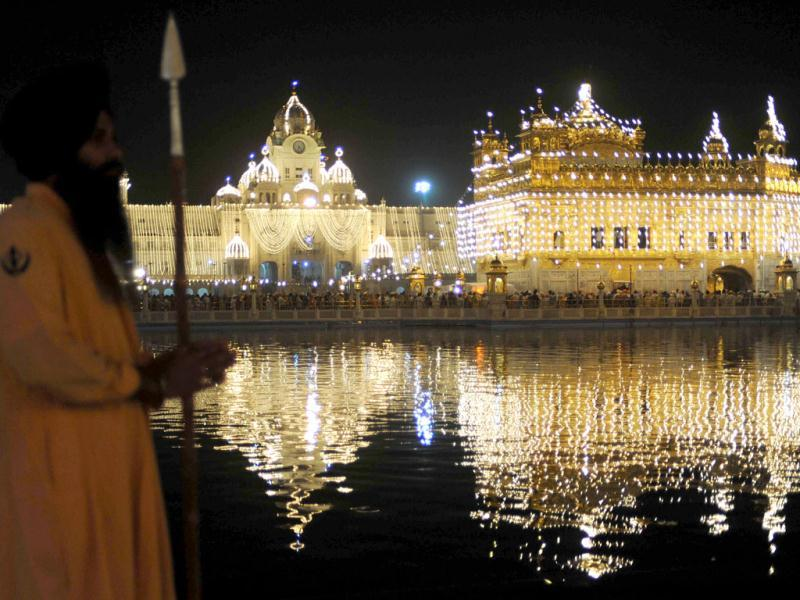 Sikh devotees pay their respects at the illuminated Golden Temple on the eve of Diwali in Amritsar. (AFP)