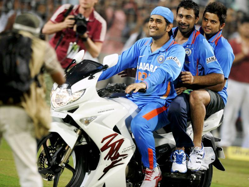 Indian cricket captain Mahendra Singh Dhoni (L) rides a bike he won as the man of the tournament as teammates Praveen Kumar (C) and Suresh Raina ride with him after winning the final ODI match against England at Eden Gardens in Kolkata. (AFP)