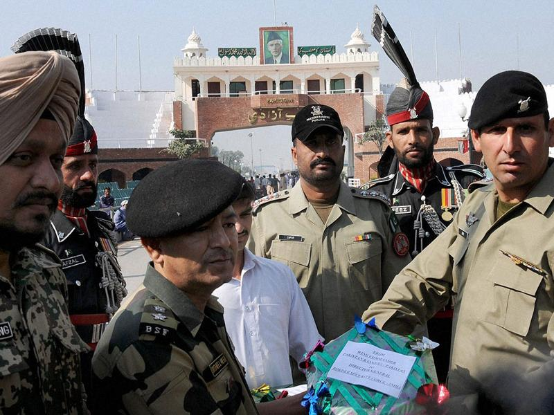 BSF's officiating commandant Sushil Negi handing over sweets to Superintendent of Pak Rangers on the occasion of Diwali at Attari International Border.