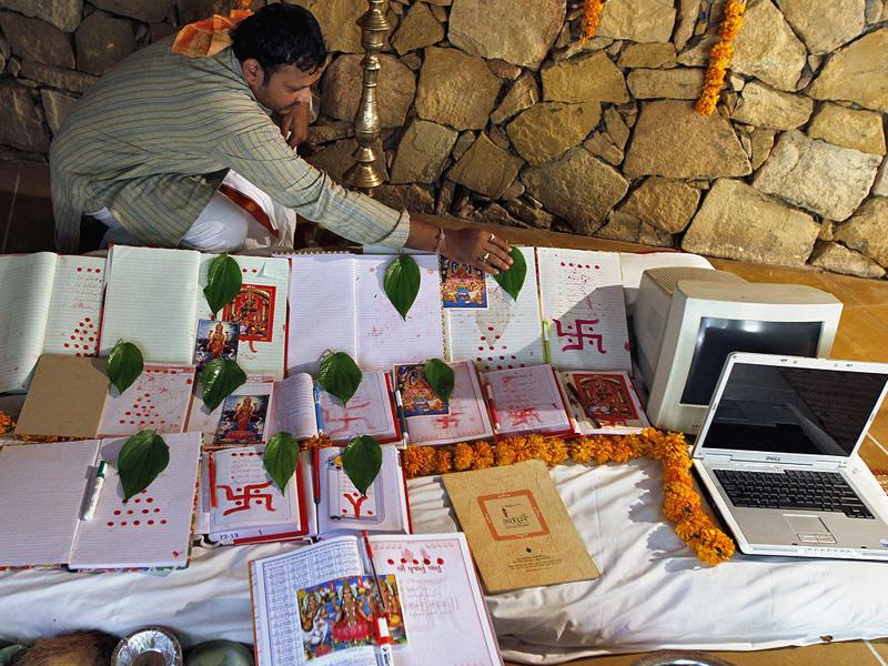 A Hindu priest places leaves on record-keeping books as part of a ritual to worship the Hindu goddess of wealth Lakshmi during the Hindu festival of lights Diwali in the western Indian city of Ahmedabad. The ritual, also known as