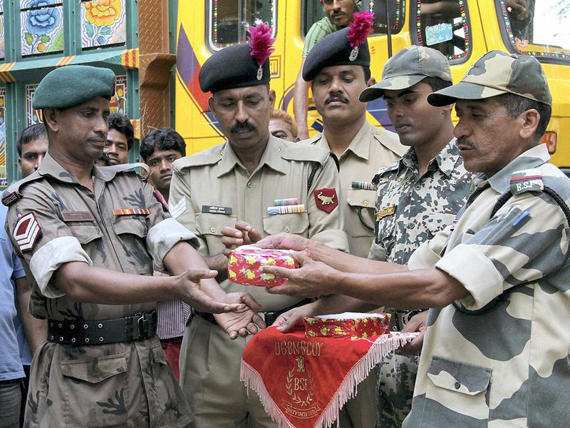 Bangladesh Rifles personnel (L) and Indian Border Security Force personnel greet each other with sweets on the occasion of Diwali festival, at the Akhaura check-post on the outskirts of Agartala.