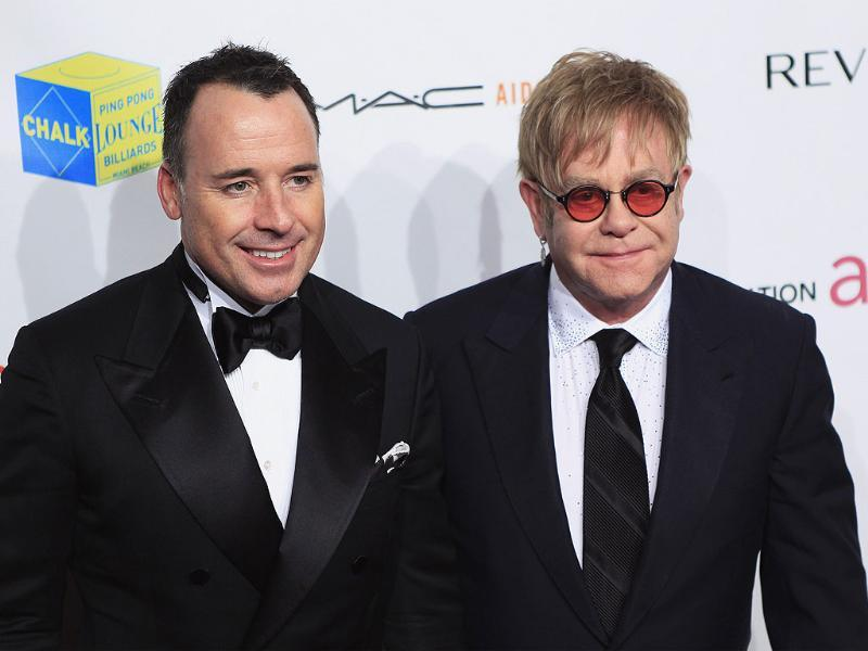 Singer Elton John (R) and his partner David Furnish arrive at a benefit for the Elton John AIDS Foundation in New York.