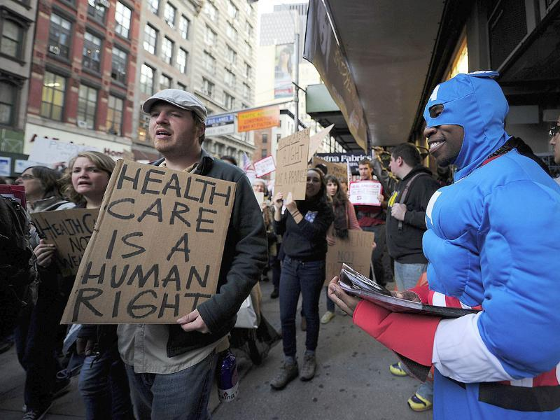 Occupy Wall Street supporters march past a Halloween store's employee dressed as Captain America while calling for universal healthcare, in New York.