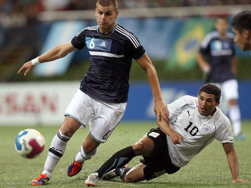 Argentina's Leandro Gonzalez, left, dribbles past Uruguay's Tabare Viudez during a men's soccer semifinal match at the Pan American Games in Guadalajara, Mexico.