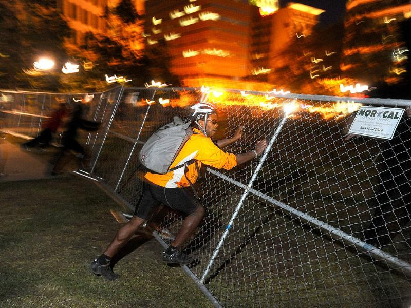 An Occupy Oakland protester tears down a fence outside City Hall in Oakland, California.