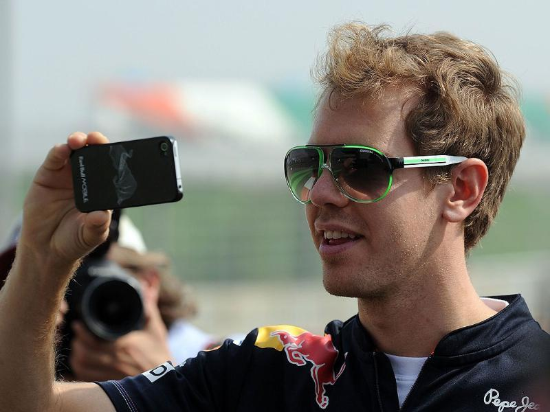 Red Bull-Renault driver Sebastian Vettel of Germany takes pictures while inspecting the track with his team officials one day before the practice sessions of Formula One's Indian Grand Prix at the Buddh International circuit in Greater Noida.