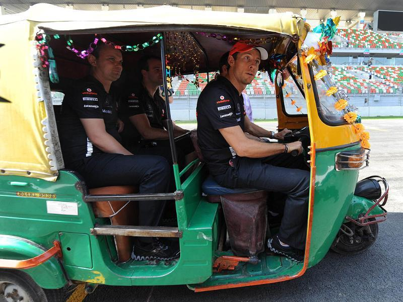 McLaren-Mercedes driver Jenson Button (R) of Britain drives an autorickshaw as he inspects the circuit one day before the practice sessions of Formula One's Indian Grand Prix at the Buddh International circuit in Greater Noida.