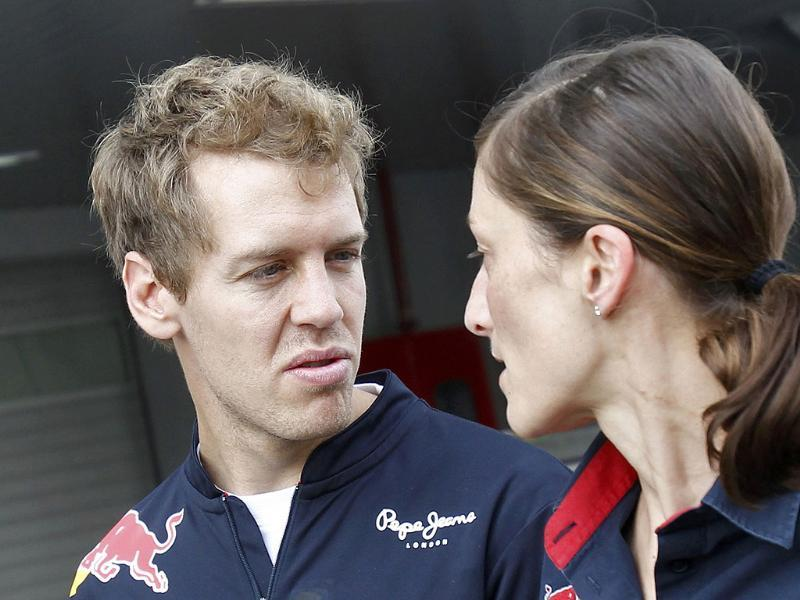 Red Bull Formula One driver Sebastian Vettel (L) of Germany talks with a teammate in the paddock area at the Buddh International Circuit in Greater Noida.