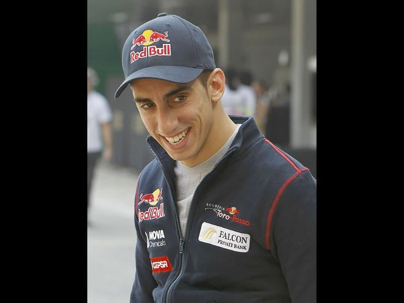 Toro Rosso Formula One driver Sebastien Buemi of Switzerland smiles as he arrives in the paddock area at the Buddh International Circuit in Greater Noida.