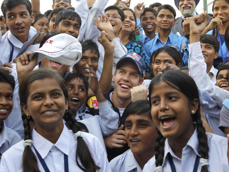 Red Bull driver Sebastian Vettel of Germany (C) poses with local students during an event at the Indian Formula One Grand Prix at the Buddh International Circuit in Greater Noida. (AP)