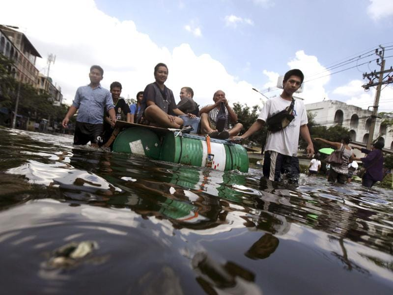 Thai residents ride a makeshift raft as they leave flooded area in Bangkok, Thailand. (AP)