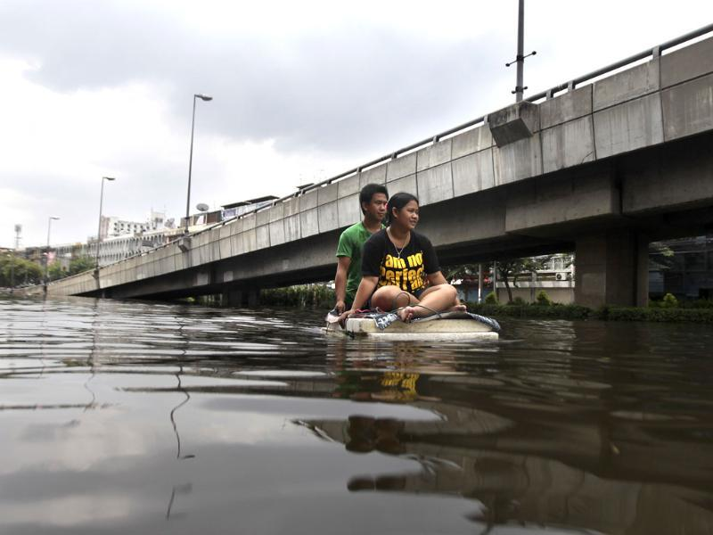 Thai residents ride a makeshift boat as they leave flooded area in Bangkok, Thailand. (AP)