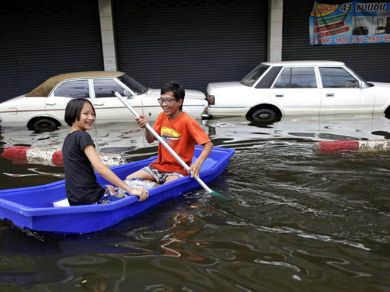 A couple paddle the boat past partially submerged cars in flooded central Bangkok. (Reuters)