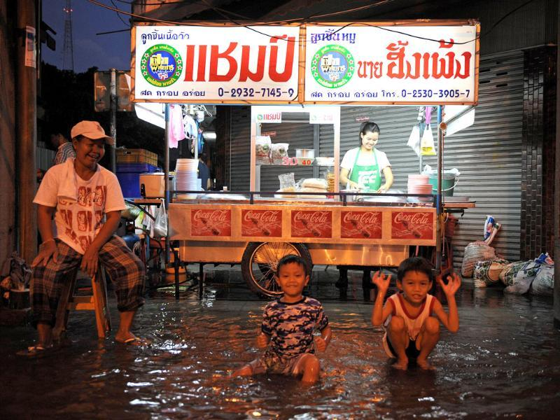 Children play in floodwaters near a street food stall near the Chao Phraya river in central Bangkok. (AFP)