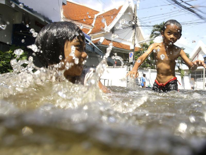 Thai children play along a flooded area in Bangkok. (AP)